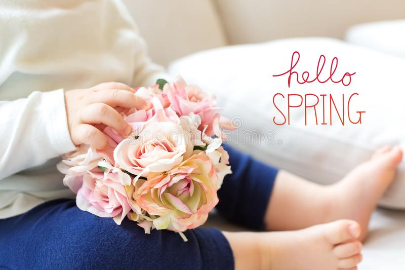Hello Spring message with toddler boy with flowers. On a couchr royalty free stock photography