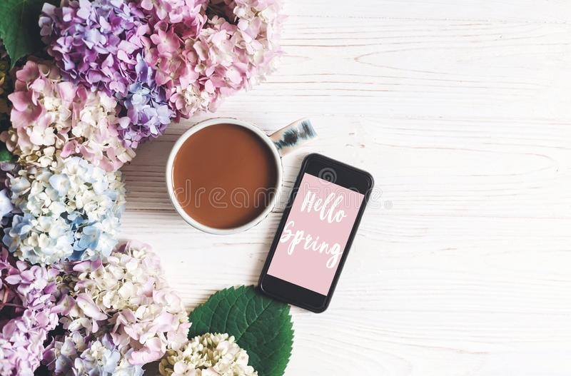 Hello Spring text sign on phone screen and beautiful hydrangea flowers and coffee cup on rustic white wooden table, flat lay. Stylish floral greeting card stock photography