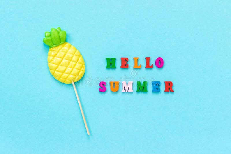 Hello summer colorful text, pineapple lollipop on stick on blue paper background. Concept vacation or holidays Creative Top view stock photos