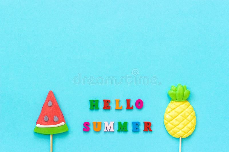 Hello summer colorful text, pineapple and watermelon lollipops on stick on blue paper background. Concept vacation or holidays. Creative Top view Copy space stock images