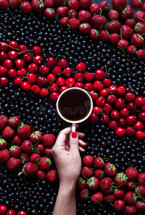 Hello summer. A cup of black coffee in a female hand on a black background with summer berries: strawberries, currants. Hello summer harvest. A cup of black royalty free stock photos