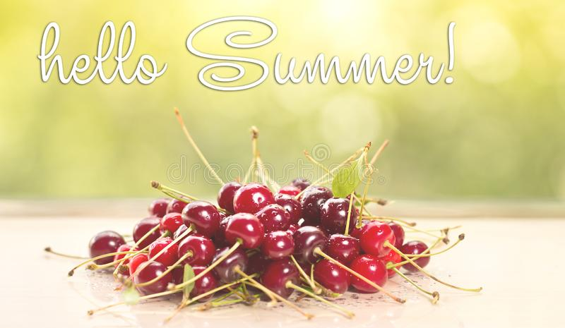 HELLO SUMMER  greeting card. fresh cherries on wooden table royalty free stock photo