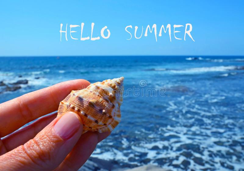 Hello Summer greeting card with hand holding sea shell on a blue ocean water background. stock image