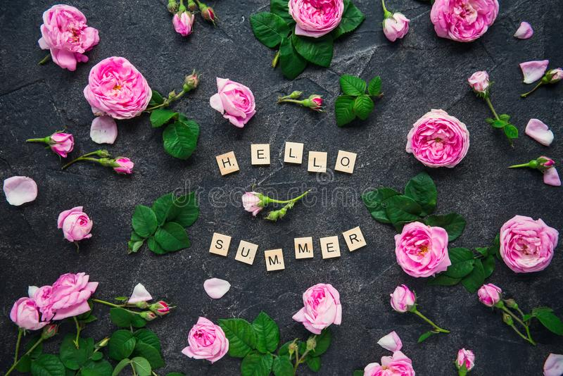 Hello Summer inscription by wooden letters and fresh spring pink tea rose flowers on dark stone background. Lettering summer seaso royalty free stock photos
