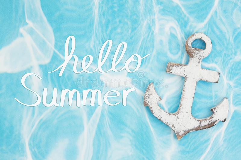 Hello Summer message with weathered anchor on a turquoise paper stock images