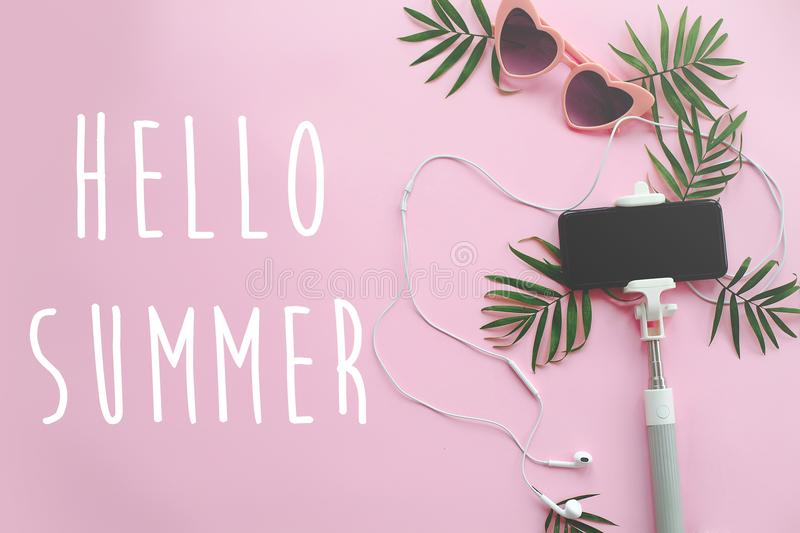 Hello Summer text on stylish pink sunglasses, phone on selfie st. Ick, headphones, and green palm leaves on pink background. stylish summer vacation flat lay royalty free stock photography