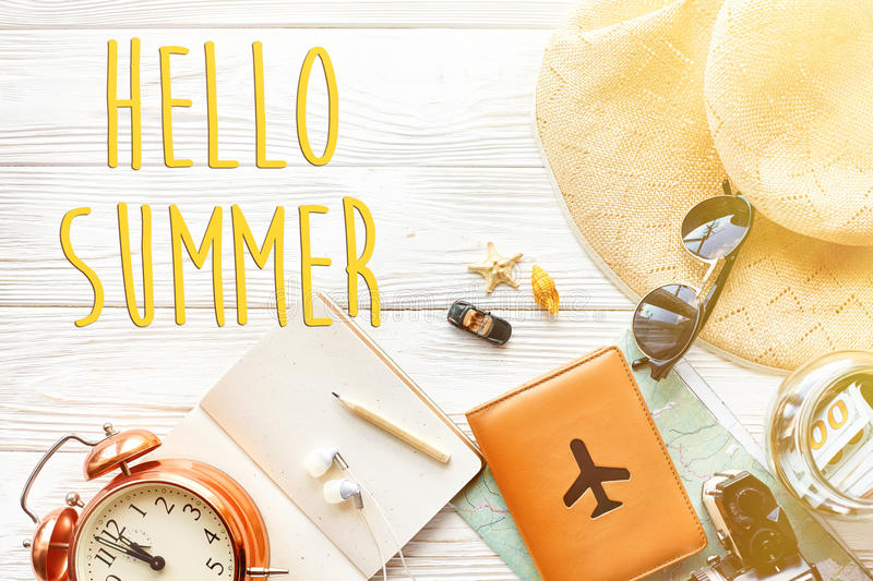 Hello summer text, time to travel concept, space for text. map c. Amera passport money phone sunglasses and clock hat shells car toy on white wooden background royalty free stock images