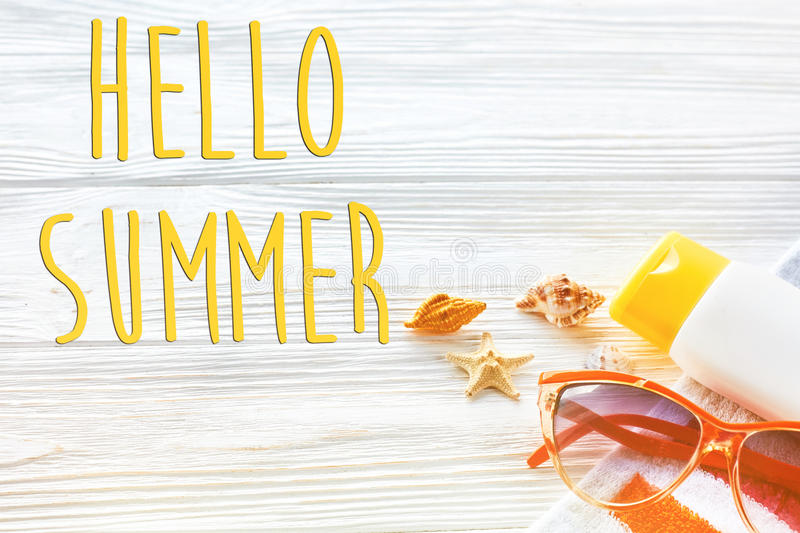 hello summer text, vacation concept. colorful towel, sunglasses, yellow sunscreen and star shells on white rustic wooden royalty free stock photos