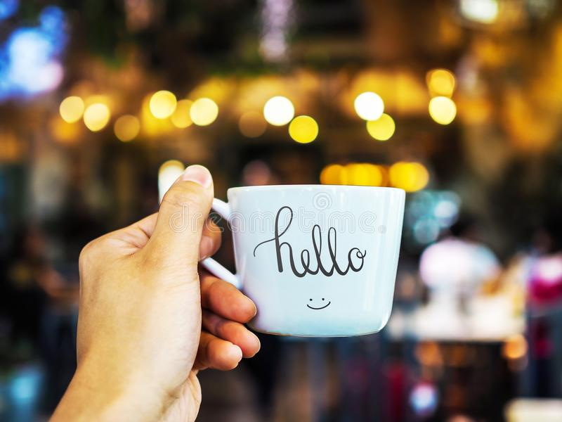 Hello text hand writing on cup with hand holding stock photos