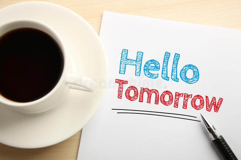 Hello Tomorrow. Text Hello Tomorrow written on the white paper with pen and a cup of coffee aside stock photos