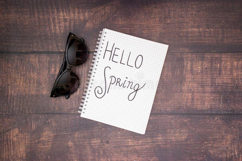 Hello vår - blomma och solglasögon på trätabellen royaltyfri fotografi
