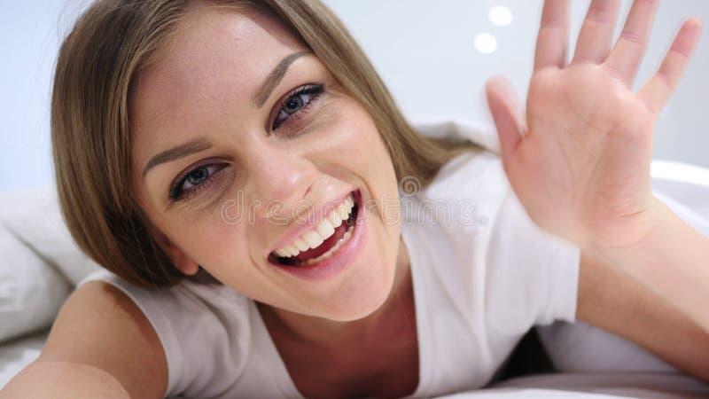 Hello, Welkom hetende Vrouw in Bed Golvende Hand, Online Videopraatje stock afbeelding