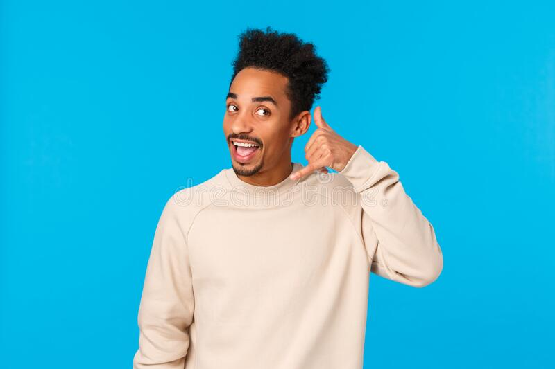 Hello whos calling. Funny attractive and cheerful hipster african american guy with afro haircut, moustache, imitating. Phone-call making mobile gesture near stock image