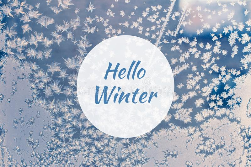 Hello winter greeting card with blue frosted window and frozen snowflakes closeup stock images