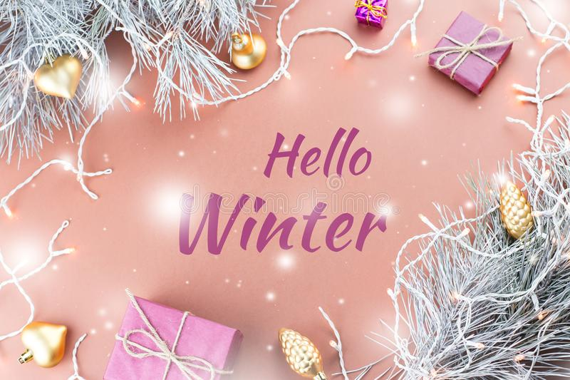 Hello Winter greeting card with fir tree, purple giftboxes, golden ornaments and Christmas lights in brown background. Hello Winter greeting card with fir tree royalty free stock photography