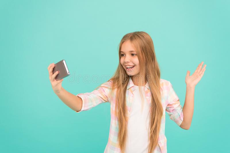 Hello world this is my channel. Let me take selfie. Child girl hold smartphone. Video call concept. Girl hold smartphone royalty free stock photography