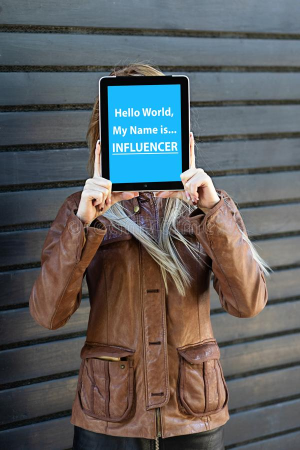 """""""Hello world, my name is influencer"""" text on tablet in young blogger woman hands. stock photos"""