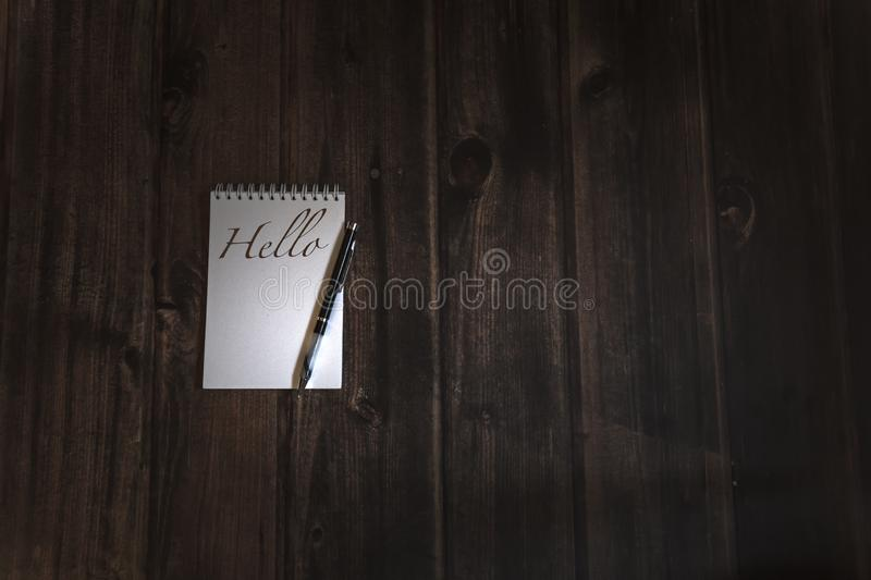 Opened notebook on wooden table. `hello` writing on lear white notebook paper by black pen, wooden rustic table, message handwritten royalty free stock images