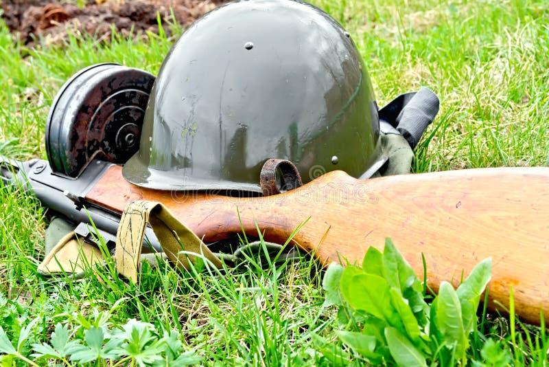 Helm en machinepistool op gras stock afbeelding