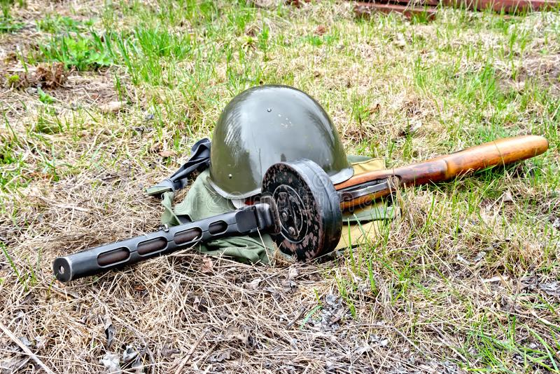 Helm en machinepistool op grond stock fotografie