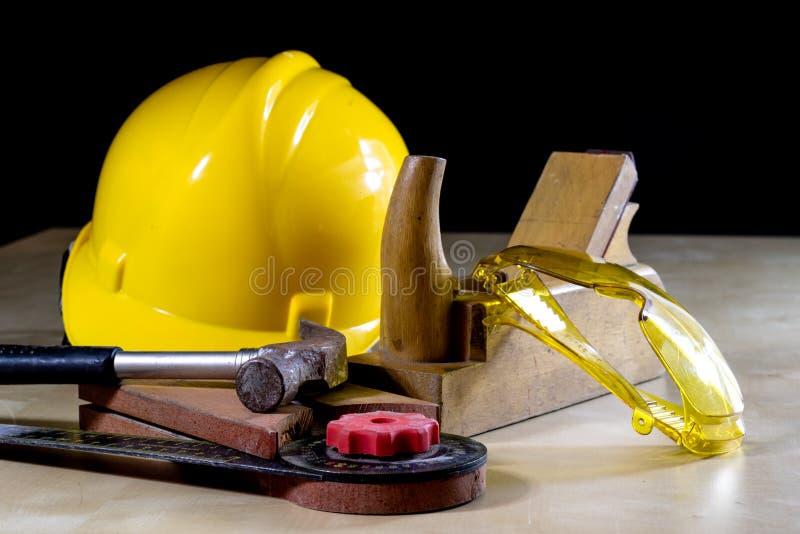 Helm en timmermanshulpmiddelen op de werkbank Glazen, hamer en stock fotografie