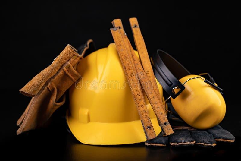 Helm, handschoenen en lepel op een donkere werkbank Veiligheid en hygi?netoebehoren voor bouwvakkers stock afbeelding