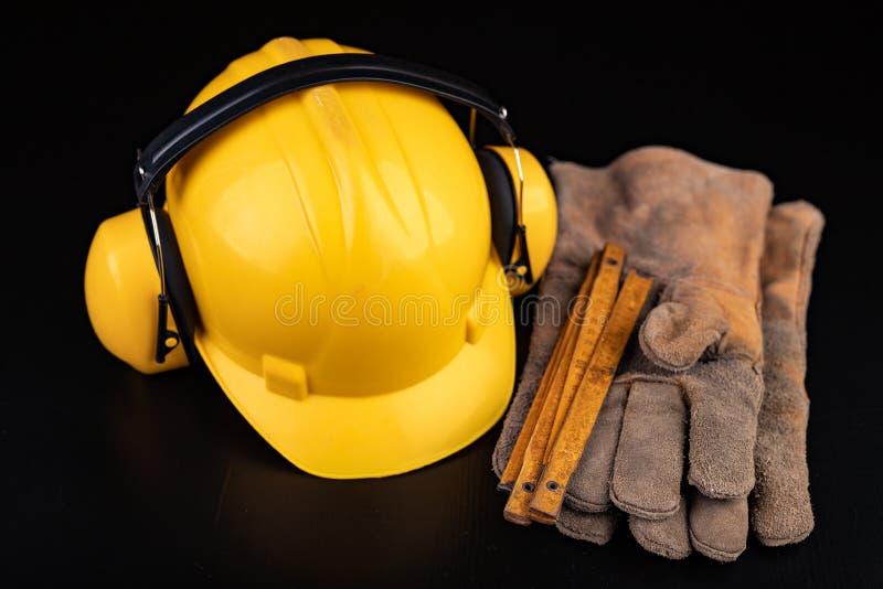 Helm, handschoenen en lepel op een donkere werkbank Veiligheid en hygi?netoebehoren voor bouwvakkers royalty-vrije stock foto's