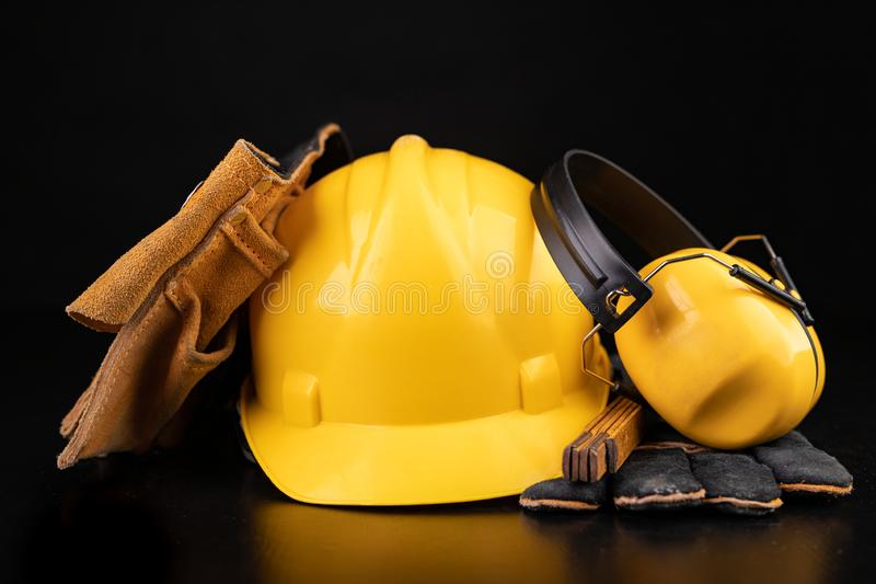 Helm, handschoenen en lepel op een donkere werkbank Veiligheid en hygi?netoebehoren voor bouwvakkers stock afbeeldingen