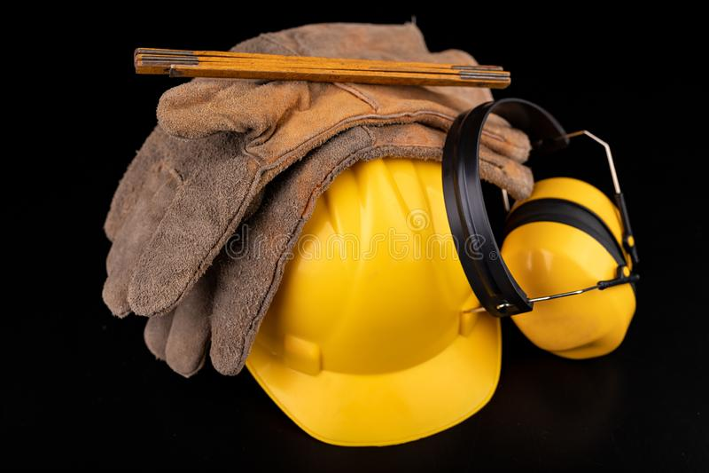 Helm, handschoenen en lepel op een donkere werkbank Veiligheid en hygi?netoebehoren voor bouwvakkers royalty-vrije stock foto