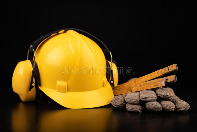 Helm, handschoenen en lepel op een donkere werkbank Veiligheid en hygi?netoebehoren voor bouwvakkers royalty-vrije stock afbeelding
