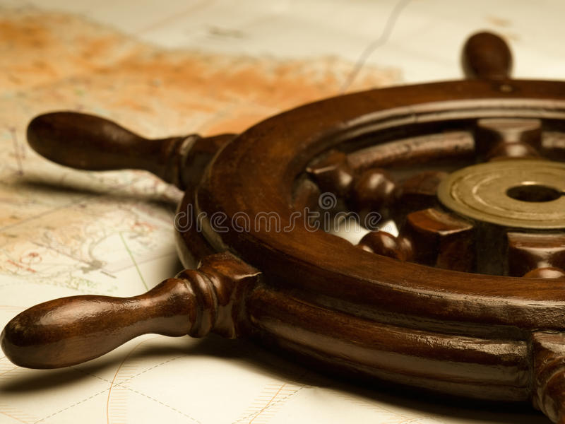 Helm and navigation map royalty free stock photo