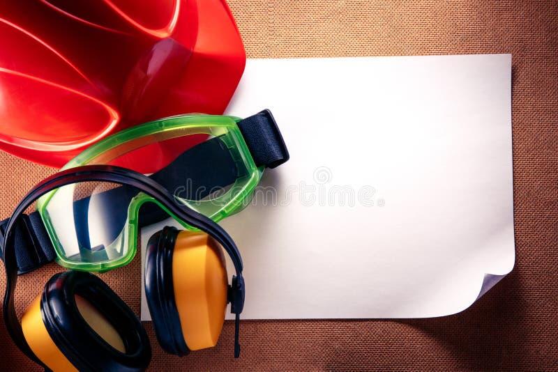 Helm, oortelefoons, beschermende brillen en leeg document royalty-vrije stock afbeeldingen