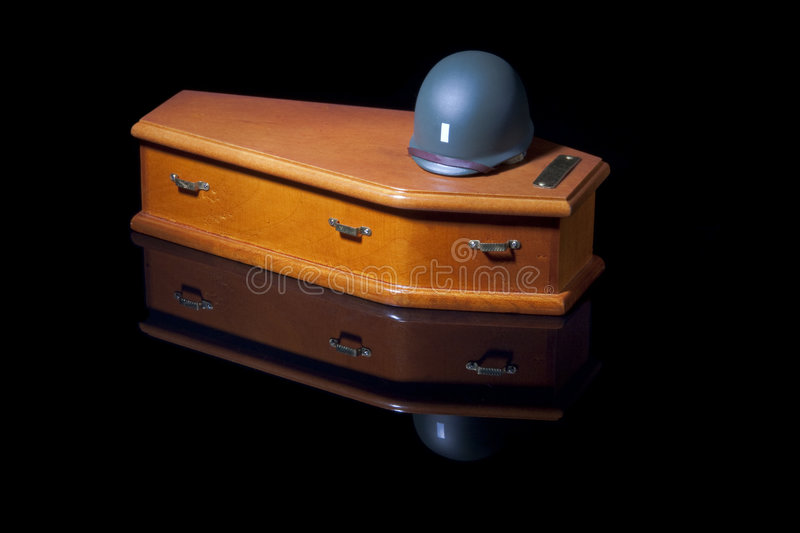 Helmet on Coffin. An army lieutenant's helmet on a coffin. Spotlighted on a black background with the reflection clearly visible. Conceptual image for all of royalty free stock photography