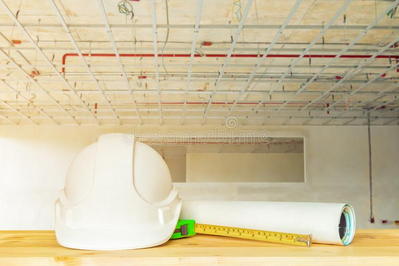 helmet plastic white with dart and measuring tape green on wood table in interior Construction site stock image