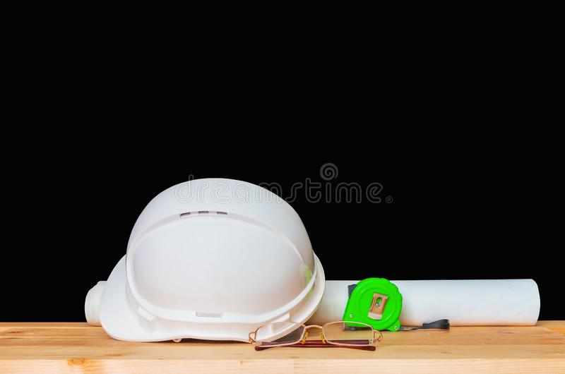 Helmet plastic white with glasses, paper roll plan blueprint and measuring tape concept construction on Wooden stock image