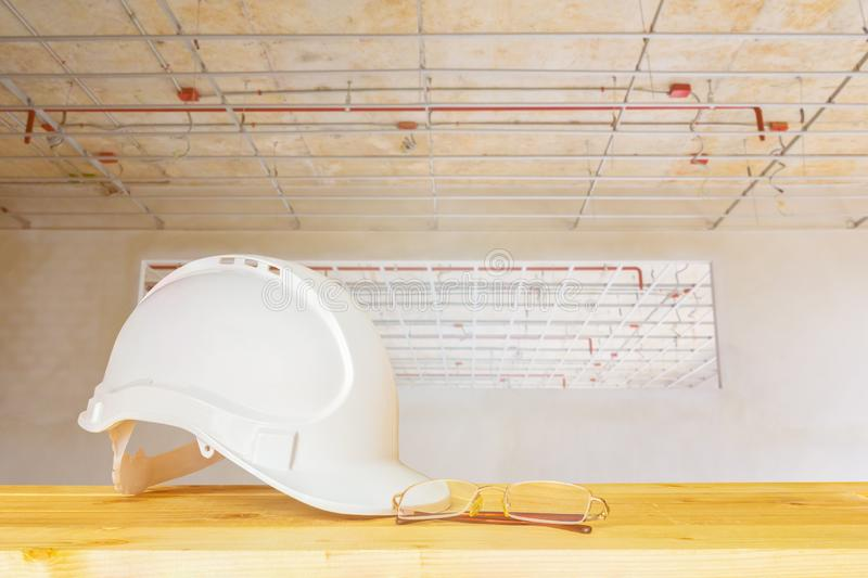 Helmet plastic white with glasses on wood table in interior Construction site building housing stock photography