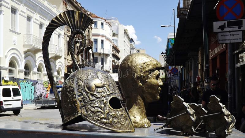 Helmet of a Spartan warrior, Athens, Greece. ATHENS, GREECE – MAY 1, 2014: Flea Market in the center of Athens. A helmet of a Spartan Warrior and a bust royalty free stock photography