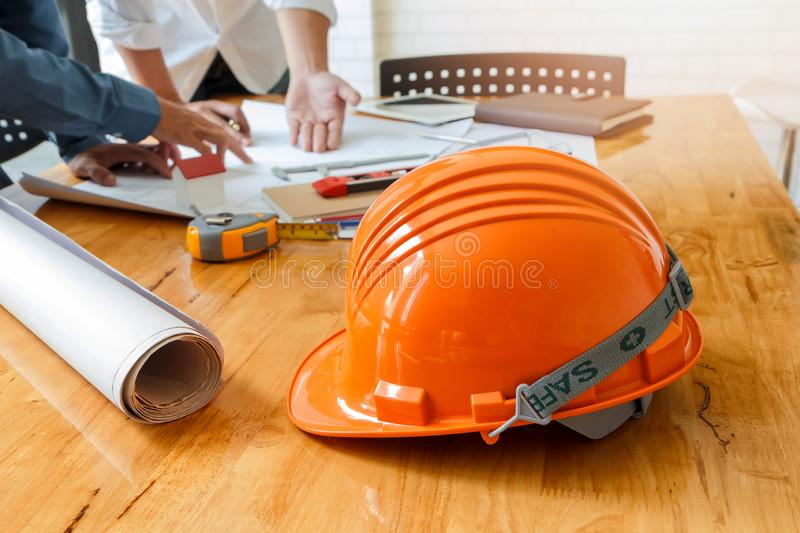 Helmet on wooden desk with architect royalty free stock image