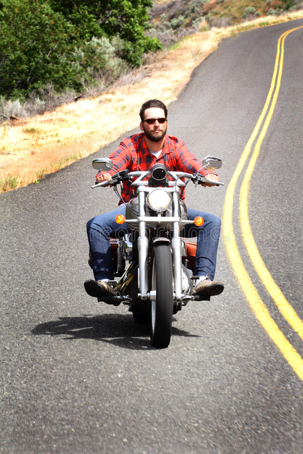 Helmetless Biker Rides Curvy Road stock photo