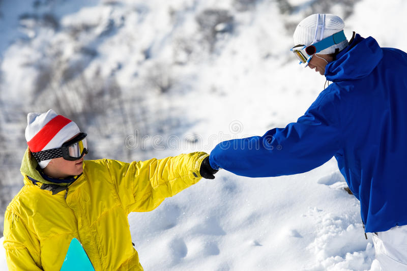 Help. Portrait of two guys with snowboards climbing down snow-covered mountain royalty free stock photo