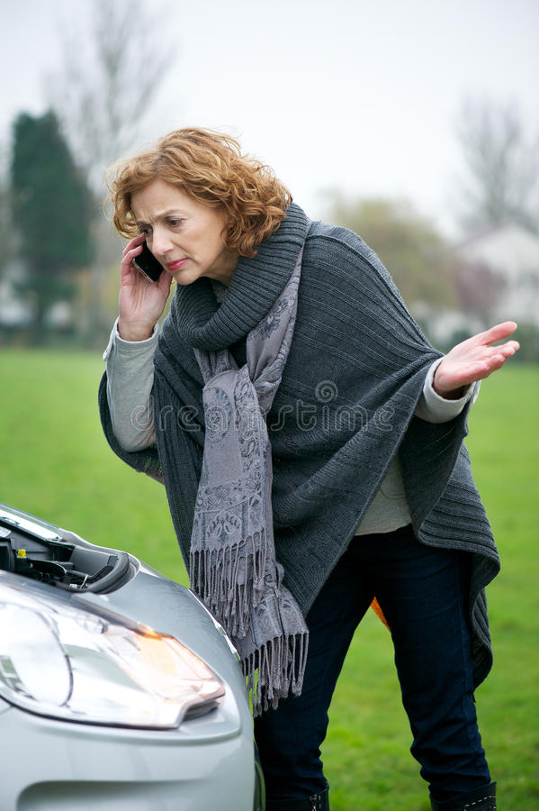 Help from Automobile Customer Service. Caucasian woman on the mobile phone outdoors and communicating with automobile customer service department stock image