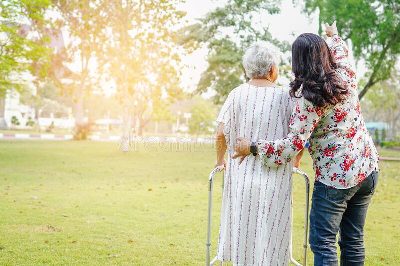 Help and care Asian senior or elderly old lady woman use walker with strong health while walking at park stock photography