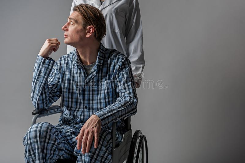 Nurse pushing tranquil cripple in wheelchair stock images