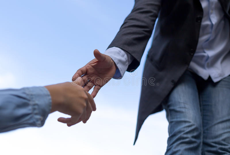 Help concept hand reaching out to help someone with blue sky stock photos