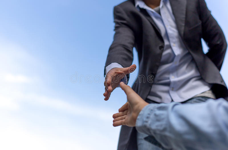 Help concept hand reaching out to help someone with blue sky stock image