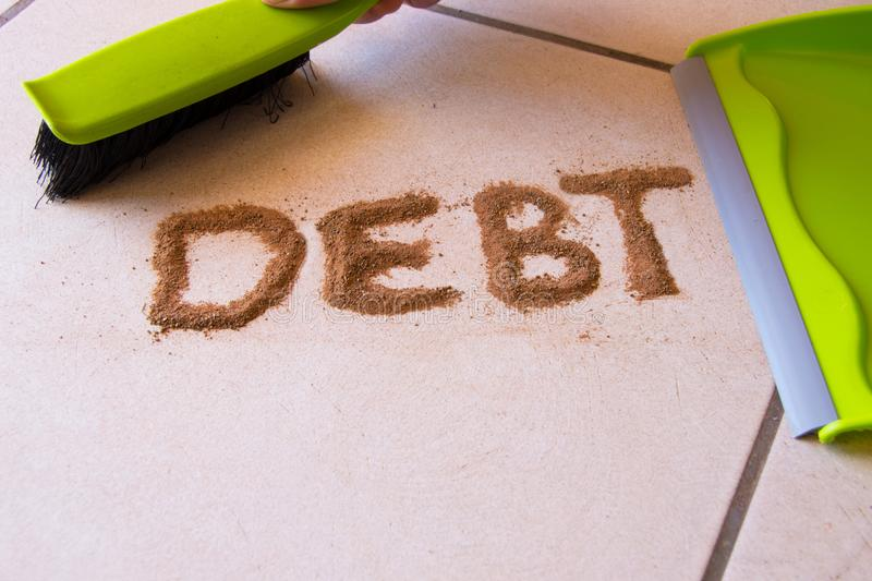 Help with Debt. Concept with debt written in dirt on a floor and a person is about to sweep the debt dirt in a dust pan using a small hand broom stock photos