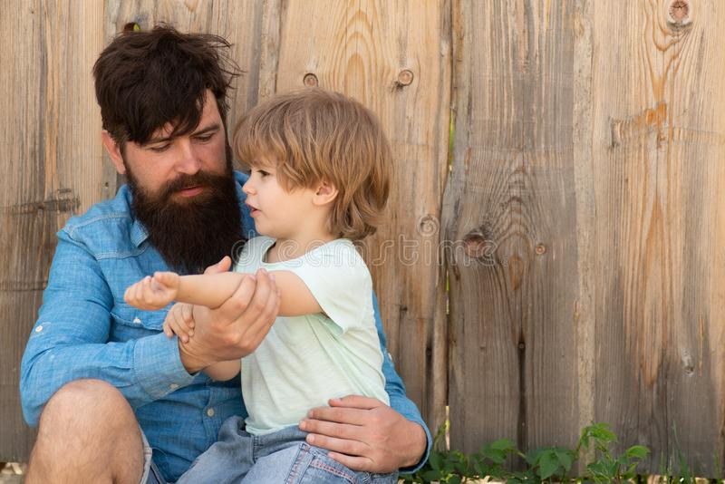 Help. Father and son with wound on the arm. Abrasion, bruising and injuries. Summer in nature. Father helps boy. royalty free stock images