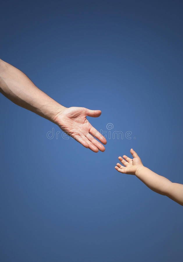 Help hand. The children's hand reaches for a daddy's hand against the blue sky stock photo
