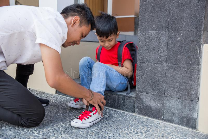 Help his son to put on his shoes royalty free stock photography
