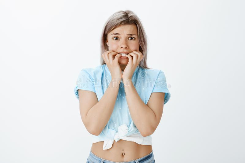 Help, I am shaking from fear. Scared timid cute girl with fair hair in cropped t-shirt, biting fingernails and frowning. Feeling anxious or nervous, being stock photo